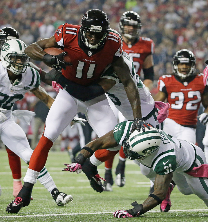 . Atlanta Falcons wide receiver Julio Jones (11) is hit by New York Jets free safety Antonio Allen (39) and New York Jets cornerback Antonio Cromartie (31) during the first half of an NFL football game, Monday, Oct. 7, 2013, in Atlanta. (AP Photo/David Goldman)