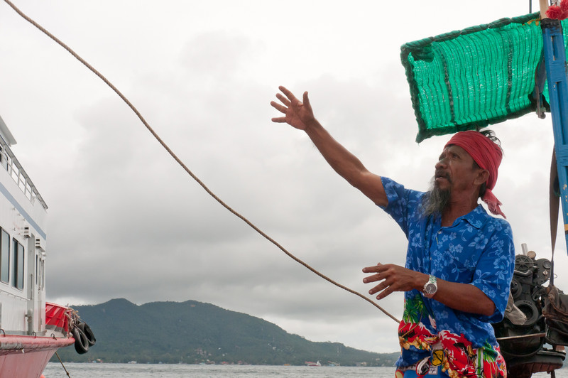 Man tossing rope onto a boat in Ko Samui, Thailand