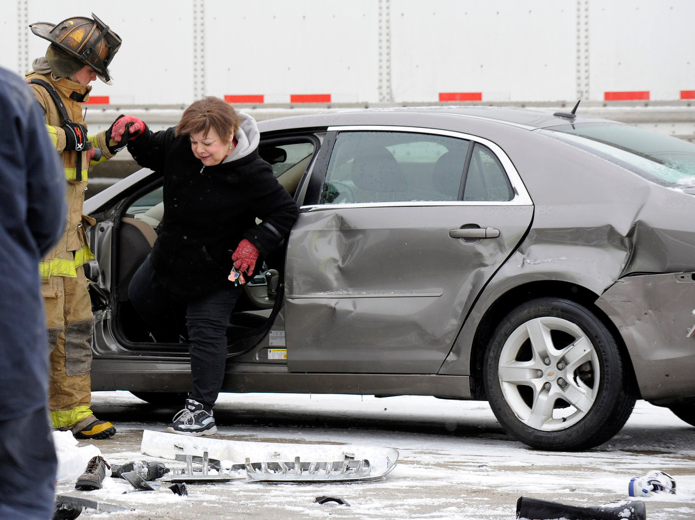 Description of . A firefighter helps a woman out of a car as emergency personnel responds to a multi-vehicle accident on Interstate 75  in Detroit, Thursday, Jan. 31, 2013. Snow squalls and slippery roads led to a series of accidents that left at least three people dead and 20 injured on a mile-long stretch of southbound I-75. More than two dozen vehicles, including tractor-trailers, were involved in the pileups. (AP Photo/The Detroit News, David Coates)
