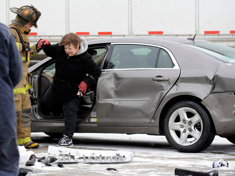 . A firefighter helps a woman out of a car as emergency personnel responds to a multi-vehicle accident on Interstate 75  in Detroit, Thursday, Jan. 31, 2013. Snow squalls and slippery roads led to a series of accidents that left at least three people dead and 20 injured on a mile-long stretch of southbound I-75. More than two dozen vehicles, including tractor-trailers, were involved in the pileups. (AP Photo/The Detroit News, David Coates)