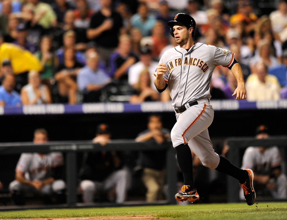. San Francisco Giants\' Brandon Belt runs home to score on an RBI single by Hector Sanchez during the fifth inning of a baseball game against the Colorado Rockies on Tuesday, Aug. 27, 2013, in Denver. (AP Photo/Jack Dempsey)