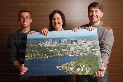 CoBuy'S Pamela Hughes, Matt Holmes Connor Freeman hold an aerial photo of the waterfront properties around Meydenbauer Bay in Bellevue, Wash.
