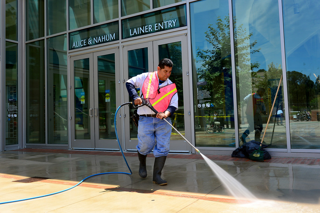 . Rafael Batres power washes dirt from the entrance to UCLA\'s Pauley Pavilion, Wednesday, July 30, 2014. (Photo by Michael Owen Baker/Los Angeles Daily News)