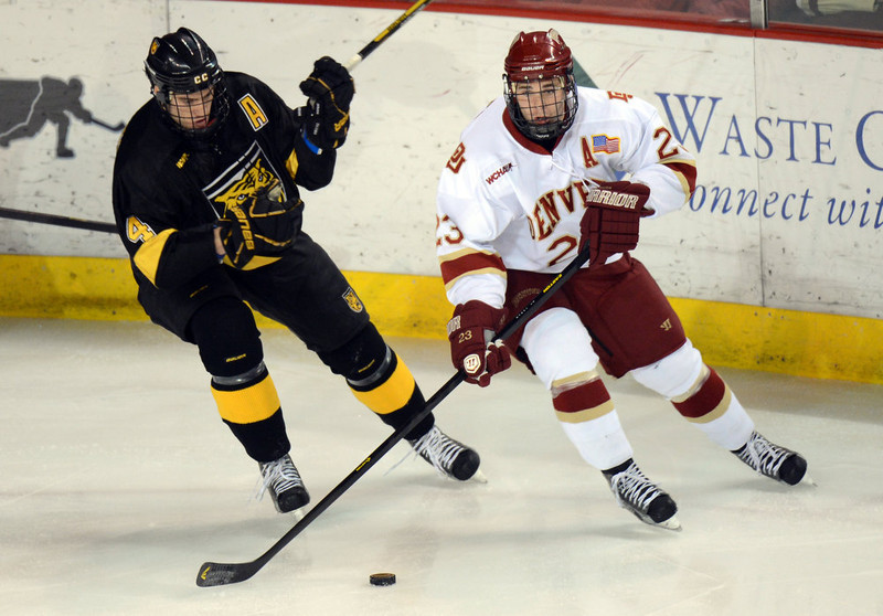 . DENVER, CO. - FEBRUARY 08: Nick Shore of University of Denver #23 controls the puck against Joe Marcino of Colorado College #4 February 8, 2013 at Magness Arena in Denver, Colorado. (Photo By Hyoung Chang/The Denver Post)