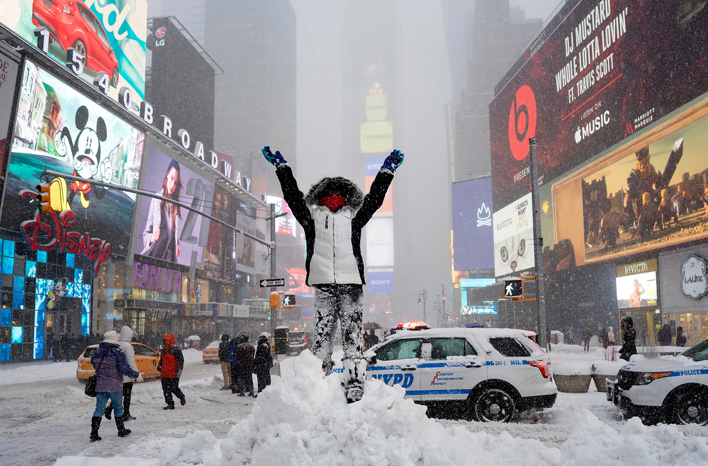 . Bella Fraker stands on a snow pile as she poses for a family photo in New York\'s Times Square, Saturday, Jan. 23, 2016, as a large winter storm rolls up the East Coast. (AP Photo/Craig Ruttle)