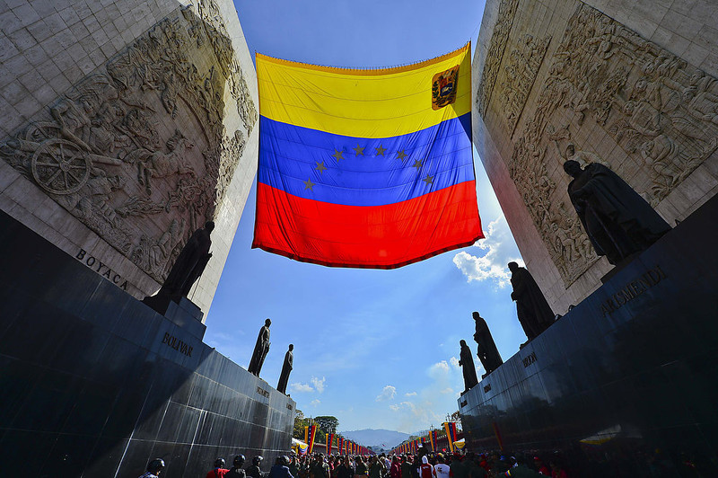 . The Venezuelan flag flies over the Monument to the Founding Fathers at the entrance to the Military Academy where the wake for late President Hugo Chavez is being held on March 7, 2013 in Caracas. The flag-draped coffin of Venezuelan leader Hugo Chavez was borne through throngs of weeping supporters as a nation bade farewell to the firebrand leftist who led them for 14 years. LUIS ACOSTA/AFP/Getty Images