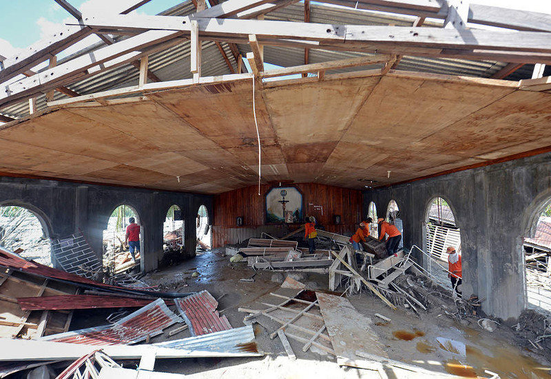 . Workers clear debris inside a church swept in by flash floods caused by Typhoon Bopha in the village of Andap in the town of New Bataan in Compostela Valley province on December 8, 2012.  Hungry and homeless typhoon survivors appealed for help on December 8 as the ravaged southern Philippines mourned its more than 500 dead and desperate people in one hard-hit town looted shops in search of food.     AFP PHOTO / TED  ALJIBE/AFP/Getty Images