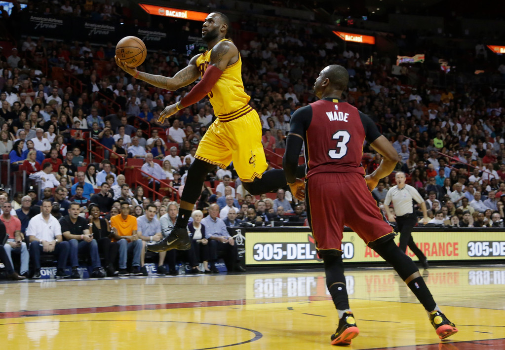 . Cleveland Cavaliers forward LeBron James, left, drives to the basket as Miami Heat guard Dwyane Wade (3) looks on during the first half of an NBA basketball game, Saturday, March 19, 2016, in Miami. (AP Photo/Lynne Sladky)