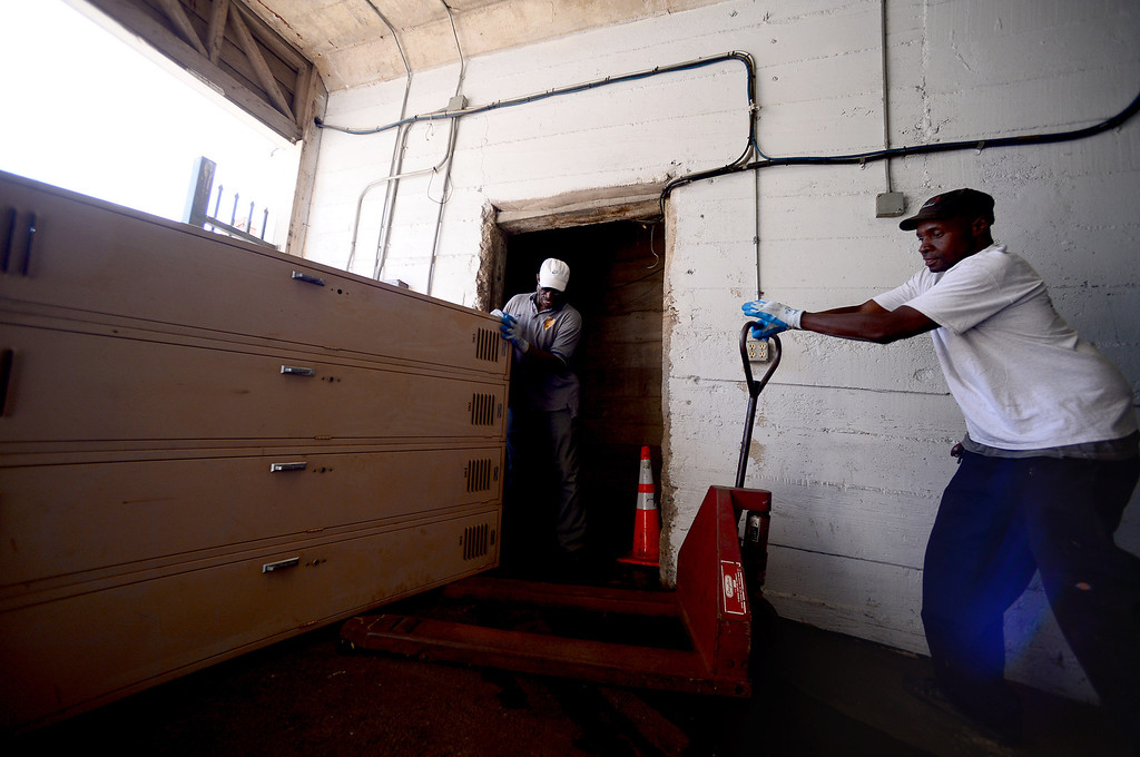 . Sylvester Ceasar and Terance Whitfield load a vintage locker into the original locker room of the Rose Bowl Stadium Thursday, June 20, 2013 in advance of the historic stadium\'s first public tours, which begin Saturday. (SGVN/Staff Photo by Sarah Reingewirtz)