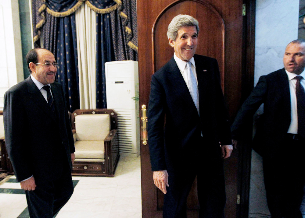 . U.S. Secretary of State John Kerry, second right, leaves after meeting with Iraq\'s Prime Minister Nouri al-Maliki, left, in Baghdad, Iraq, Sunday, March 24, 2013. Kerry made an unannounced visit to Iraq on Sunday and will urge al-Maliki to make sure Iranian flights over Iraq do not carry arms and fighters to Syria, a U.S. official said.  (AP Photo/Jason Reed, Pool)