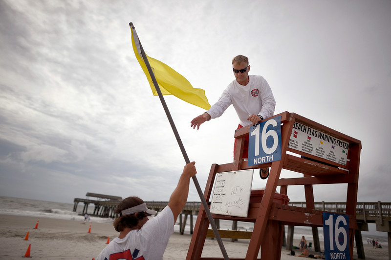 . Tybee Island Ocean Rescue Senior Lifeguard Todd Horne, right, and Mark Eichenlaub, left, hang a yellow flag that warns swimmer of strong rip currents from Hurricane Arthur along the beach, on Tybee Island, Ga., Thursday, July 3, 2014. The storm has bypassed the Georgia coast as predicted, but forecasters are warning beach goers to beware of dangerous rip currents in its wake. (AP Photo/Stephen B. Morton)