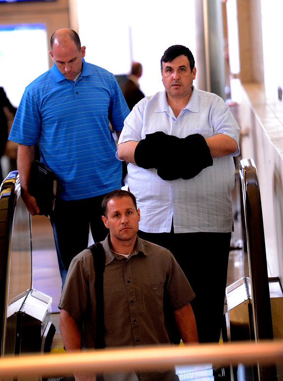 . Former SBIA developer Scot Spencer is escorted by a San Bernardino County DA investigator and an FBI agent through the John Wayne Airport in Santa Ana March 28, 2013.   GABRIEL LUIS ACOSTA/STAFF PHOTOGRAPHER.