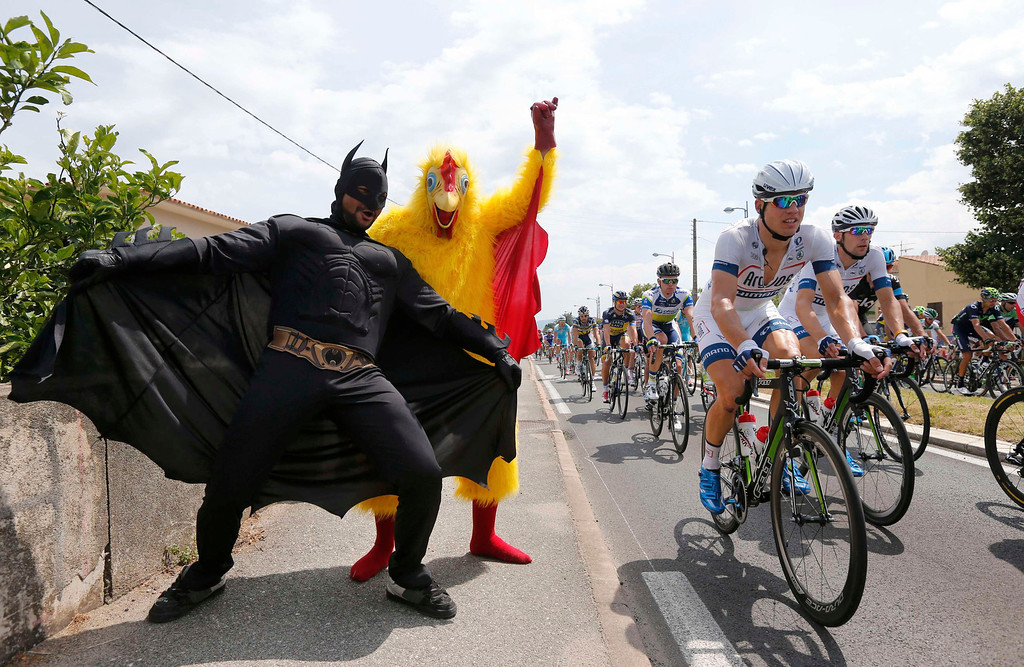 . Fans dressed in costumes cheer on the pack of riders as it cycles during the 213 km first stage of the centenary Tour de France cycling race from Porto-Vecchio to Bastia, on the French Mediterranean island of Corsica June 29, 2013.    REUTERS/Benoit Tessier