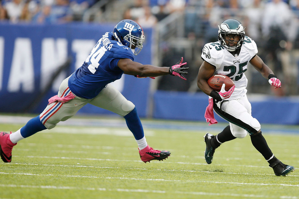 . Philadelphia Eagles\' LeSean McCoy (25) runs away from New York Giants\' Mathias Kiwanuka (94) during the first half of an NFL football game on Sunday, Oct. 6, 2013, in East Rutherford, N.J. (AP Photo/Kathy Willens)