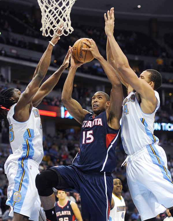 . Kenneth Faried, left, and JaVale McGee, right, converged on Atlanta forward Al Horford (15) as he drove the lane in the fourth quarter. The Denver Nuggets defeated the Atlanta Hawks 109-107 at the Pepsi Center Thursday night, November 7, 2013 for its first win of the season. Photo By Karl Gehring/The Denver Post