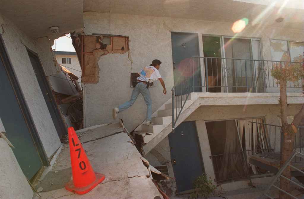 ". Robin Purcell makes his way to his daughter\'s apartment on Plummer St in Northridge to recover some of her possessions.  The Northridge quake hit at 4:31 the morning of Jan. 17, 1994, a powerful jolt that flattened buildings, destroyed homes, damaged freeways, ignited fires and disrupted water and power.  The 6.7-magnitude Northridge Earthquake also killed nearly three dozen people, injured 8,700 more, caused some $20 billion in damage and shattered the nerves of millions of Southern California residents.  ""It was like the devil was waking up ... it was a horrifying feeling,\"" said one of the quake victims quoted in a Daily News story on Jan. 18. 