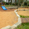sandstone block retaining wall and spinners and dual blue plastic slide on mound
