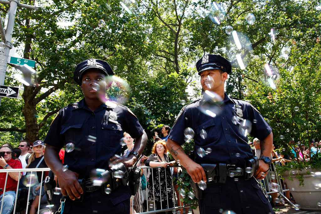 . Police officers keep watch as people take part in the Gay Pride Parade in New York June 30, 2013. REUTERS/Eric Thayer