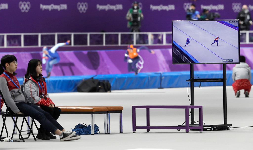 . Two volunteers, left, watch the race on a TV screen as gold medalist and new Olympic record holder Havard Lorentzen of Norway, left on screen and rear left, competes against Ronald Mulder of The Netherlands, right on screen and center rear, during the men\'s 500 meters speedskating race at the Gangneung Oval at the 2018 Winter Olympics in Gangneung, South Korea, Monday, Feb. 19, 2018. (AP Photo/Petr David Josek)