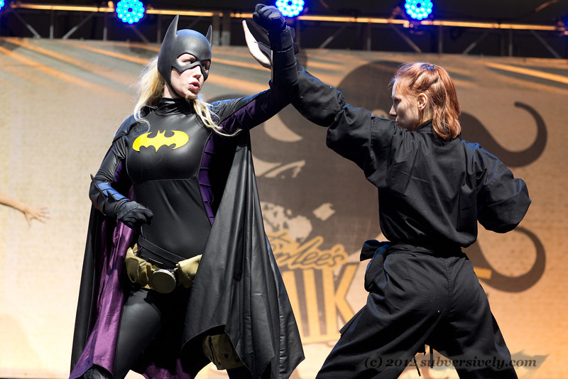 Batgirl (Marisha Ray) demonstrates a move on a ninja (Tally Justine).