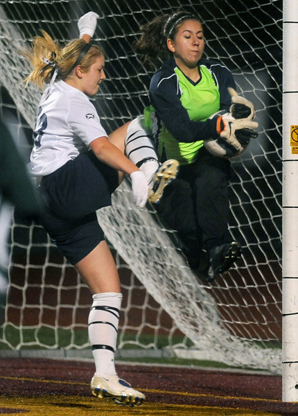 Bellarmine Prep's Kaylee Baldassin, left, charges Woodinville's goalkeeper Katrina Neir in the first half at Mount Tahoma Tuesday, Nov. 9, 2010. Joe Barrentine/Staff photographer
