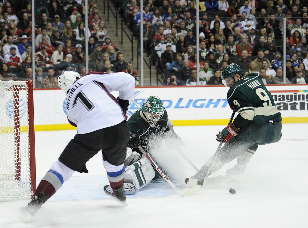 . Josh Harding #37 of the Minnesota Wild defends a shot by John Mitchell #7 of the Colorado Avalanche as Mikko Koivu #9 of the Minnesota Wild looks on during the first period of the game on November 29, 2013 at Xcel Energy Center in St Paul, Minnesota. (Photo by Hannah Foslien/Getty Images)