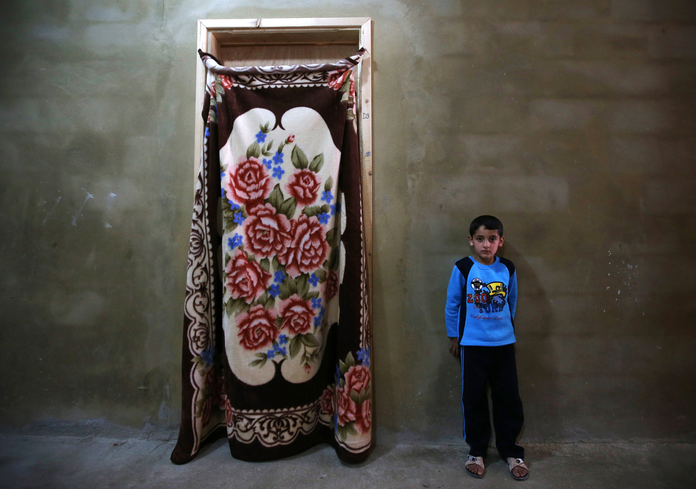 . In this picture taken on Thursday, May 29, 2014, a Syrian refugee boy stands outside his family room at a collective center, in Kirbet Daoud village in Akkar north Lebanon. (AP Photo/Hussein Malla)