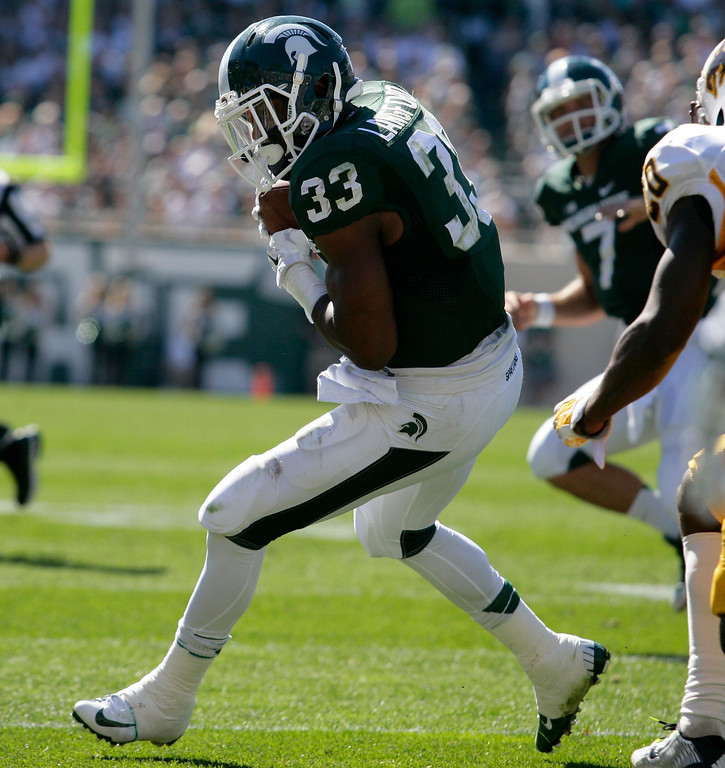 . Michigan State\'s Jeremy Langford (33) catches a pass from quarterback Tyler O\'Connor (7) during the second quarter of an NCAA college football game against Wyoming, Saturday, Sept. 27, 2014, in East Lansing, Mich. Michigan State won 56-14. (AP Photo/Al Goldis)