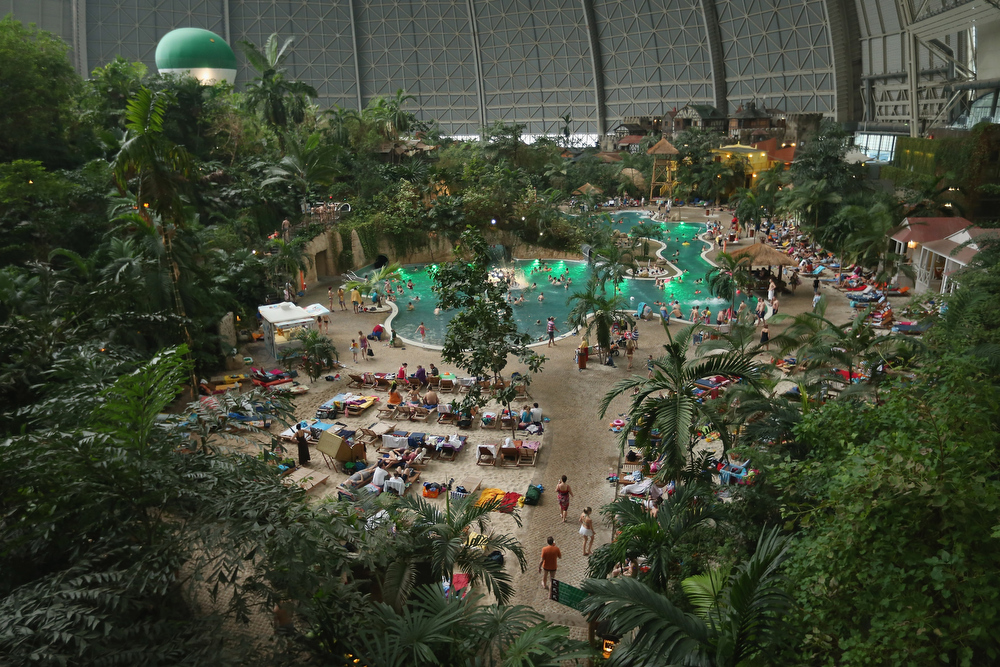 Description of . Visitors swim in a lagoon at the Tropical Islands indoor resort on February 15, 2013 in Krausnick, Germany. Located on the site of a former Soviet military air base, the resort occupies a hangar built originally to house airships designed to haul long-distance cargo. Tropical Islands opened to the public in 2004 and offers visitors a tropical getaway complete with exotic flora and fauna, a beach, lagoon, restaurants, water slide, evening shows, sauna, adventure park and overnights stays ranging from rudimentary to luxury. The hangar, which is 360 metres long, 210 metres wide and 107 metres high, is tall enough to enclose the Statue of Liberty.  (Photo by Sean Gallup/Getty Images)