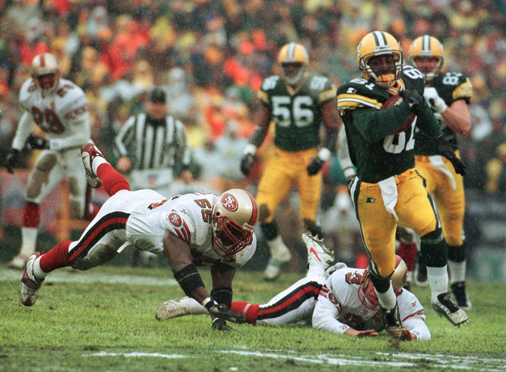 . Green Bay Packers\' Desmond Howard eludes San Francisco 49ers Kevin Mitchell (55) and punter Tommy Thompson on the way to a touchdown on a punt return in the first quarter Saturday, Jan. 4, 1997, in Green Bay, Wis. (AP Photo/David Boe)