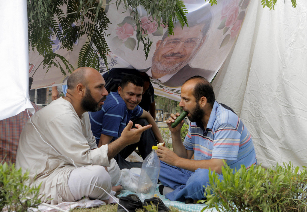 . Egyptian supporters of Egypt\'s Islamist President Mohammed Morsi eat under his poster at their camp outside of the Rabia el-Adawiya mosque near the presidential palace, in Cairo, Egypt, Tuesday, July 2, 2013. (Associated Press: Amr Nabil)
