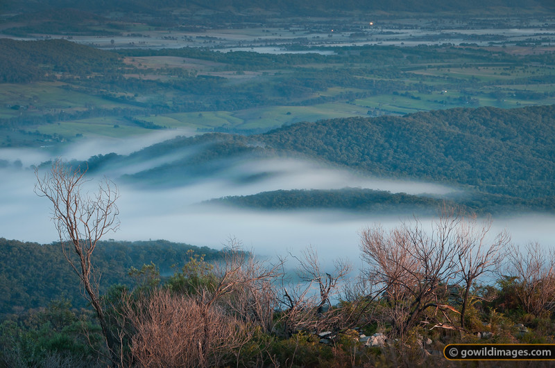 Northern view (towards Benalla) from the summit of Mt Samaria. Low, early morning clouds climb the ridges and 'burn off' into the sunlight. Their fast movement created a soft, blurred effect over the long duration of this sunrise exposure.