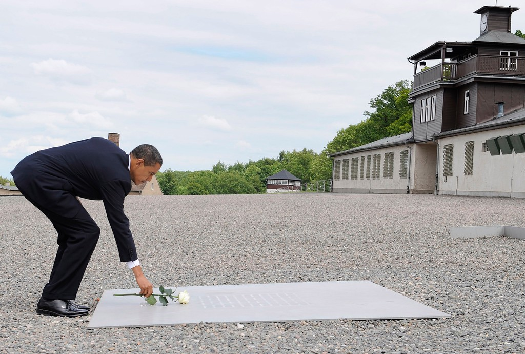 . US President Barack Obama puts down a rose in front of the gate building at the Buchenwald concentration camp near Weimar, Germany, Friday, June 5, 2009. Obama, who is en route from Egypt to France, visited Dresden before visiting the former Nazi concentration camp Buchenwald and the US regional medical center in Landstuhl during his stopover in Germany.  (AP Photo/Oliver Multhaup, pool)