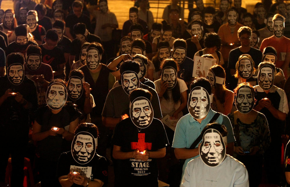 . Activists wearing masks of China\'s jailed Nobel laureate Liu Xiaobo hold candles during a night vigil at Liberty Square in Taipei June 4, 2013, on the 24th anniversary of the June 4 crackdown on pro-democracy protesters at Tiananmen Square in Beijing.  REUTERS/Steven Chen