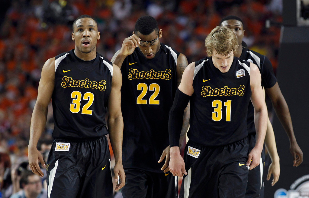 . Wichita State Shockers guard Tekele Cotton (L), forward Carl Hall (C) and guard Ron Baker leave the court for a timeout during the second half of their NCAA men\'s Final Four basketball game against the Louisville Cardinals in Atlanta, Georgia April 6, 2013. REUTERS/Jeff Haynes