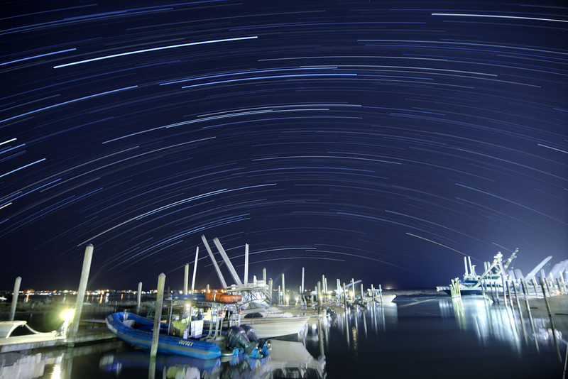 Star trails streak over the calm waters at the Crazy Sister Marina near the Marshwalk in Murrells Inlet, SC on Tuesday, April 21, 2015. Copyright 2015 Jason Barnette
