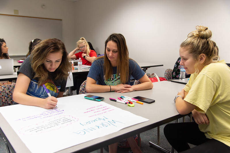 Kara Bartlett (left), Mary Ross, and Amanda House working on a memory poster in their Childhood Development course.