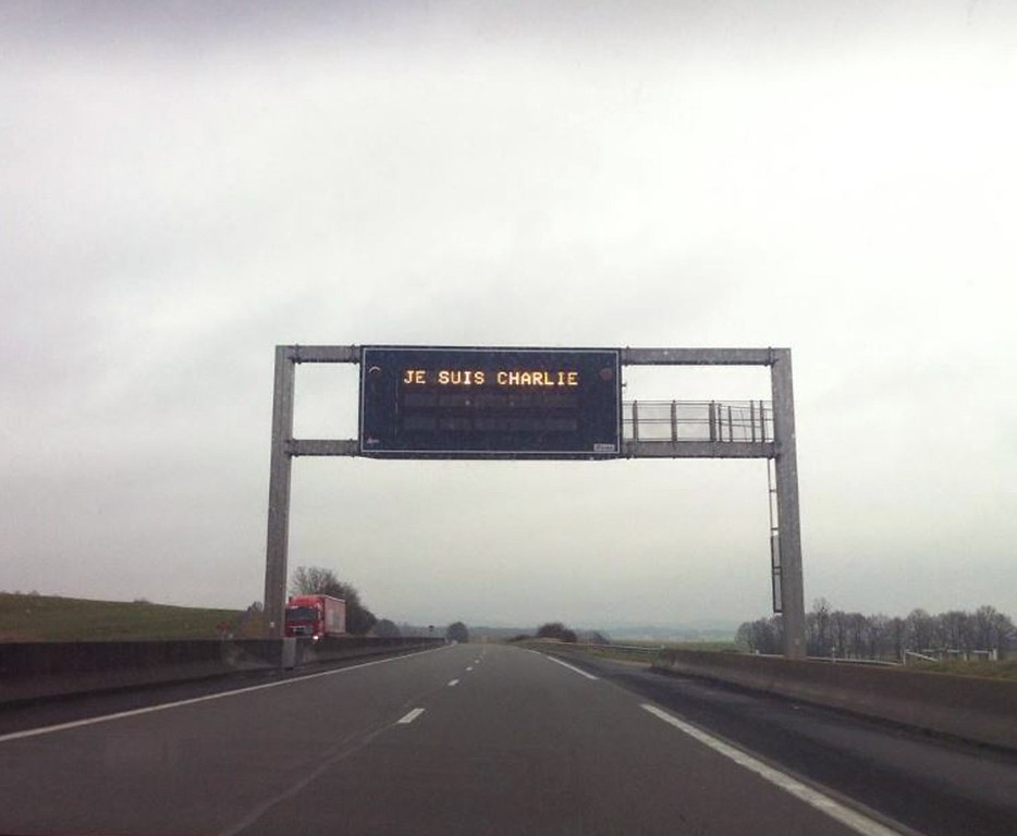 ". A handout photo taken on January 8, 2015 by Noemie Lacarelle shows an electronic highway sing near Dijon, south-east of Paris, reading ""Je suis Charlie\"" (I am Charlie). Office workers stood shoulder to shoulder, buses and metros halted, and only the toll of bells and sound of weeping broke the silence on January 8 as France honored the 12 people massacred at Charlie Hebdo magazine. \""Charlie will be free!\"" cried a woman joining a large crowd in front of Paris\' medieval Notre Dame cathedral a moment before noon (1100 GMT) when the country observed a national minute of silence.   AFP PHOTO / NOEMIE LACARELLE/AFP/Getty Images"