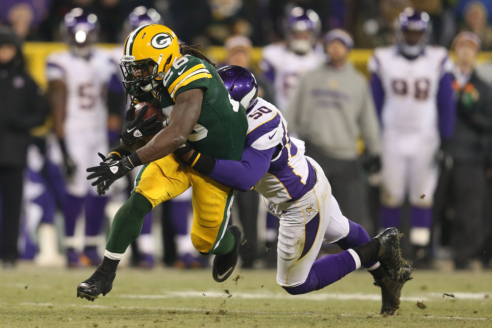 Description of . Running back DuJuan Harris #26 of the Green Bay Packers runs the ball as he is tackled by outside linebacker Erin Henderson #50 of the Minnesota Vikings in the third quarter during the NFC Wild Card Playoff game at Lambeau Field on January 5, 2013 in Green Bay, Wisconsin.  (Photo by Andy Lyons/Getty Images)