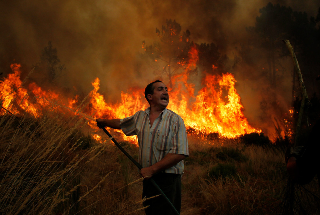 . An inhabitant uses a hose to extinguish a wildfire near Caramulo, north Portugal, Thursday, Aug. 29, 2013.  (AP Photo/Francisco Seco)