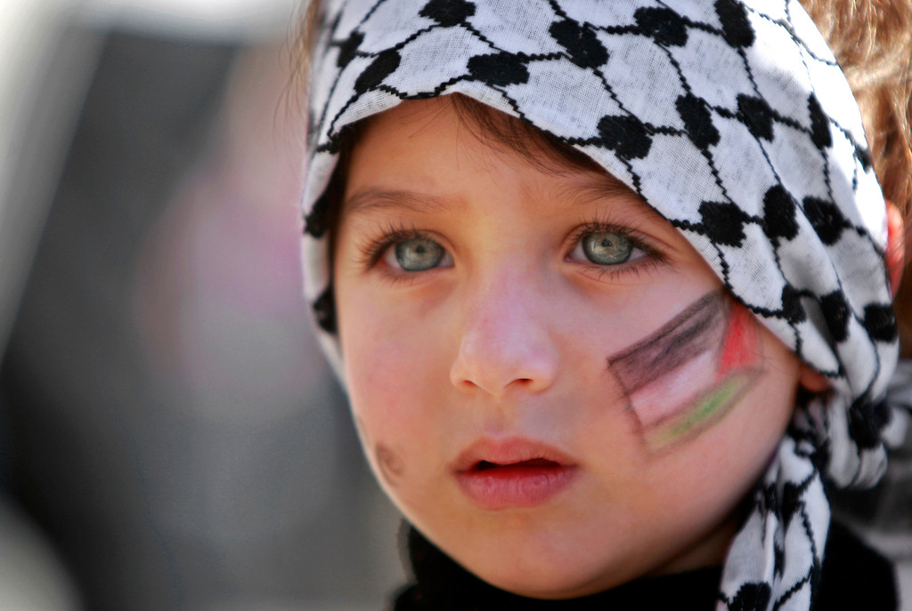 . A girl with the Palestinian flag painted  on her face attends a rally supporting the Palestinian UN bid for observer state status, in the West bank city of Ramallah, Thursday, Nov. 29, 2012. The Palestinians are certain to win U.N. recognition as a state on Thursday but success could exact a high price: delaying an independent state of Palestine because of Israel\'s vehement opposition. (AP Photo/Majdi Mohammed)