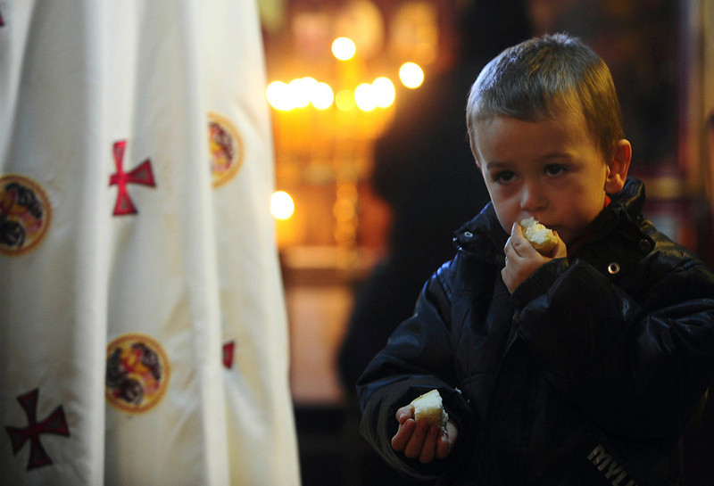 . A boy eats piece of prosphora, or offering of bread, given to him by a priest during a Christmas service in the Christian Orthodox church, St. Atanasij the Great, in the southeastern Macedonia\'s town of Bogdanci, on Monday, Jan. 7, 2013. Orthodox Christians celebrate Christmas day on January 7 because they follow the Julian Calendar, which was replaced in Western Europe by the Gregorian calendar 500 years ago. (AP Photo/Boris Grdanoski)