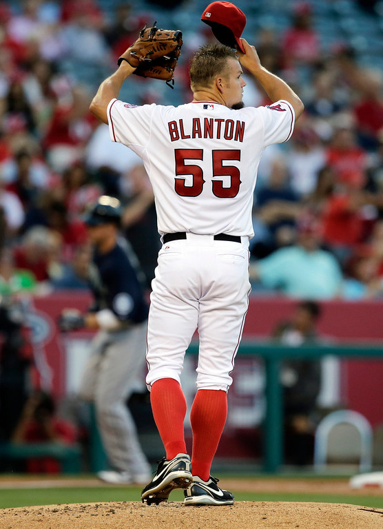 . Los Angeles Angels\' Joe Blanton watches as Seattle Mariners\' Justin Smoak, background left, rounds the bases after hitting a home run during the second inning of a baseball game in Anaheim, Calif., Tuesday, June 18, 2013. (AP Photo/Jae C. Hong)