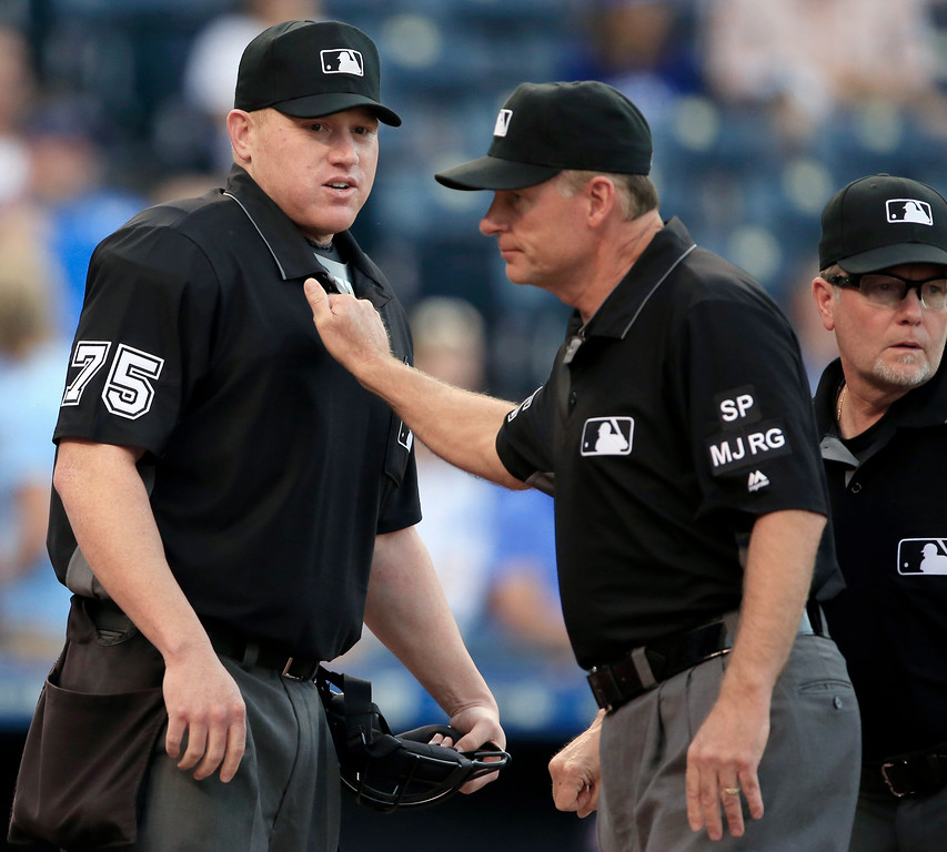 . Umpire Ed Hickox, right, wishes the best to home plate umpire Tripp Gibson (73) before a baseball game between the Kansas City Royals and the Cleveland Indians at Kauffman Stadium in Kansas City, Mo., Friday, June 2, 2017. (AP Photo/Orlin Wagner)