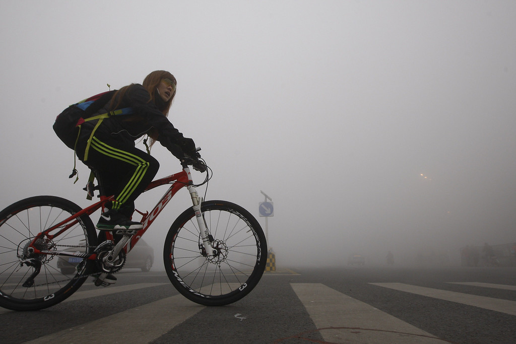 . A girl cycles on a street under heavy smog in Harbin, northeast China\'s Heilongjiang province, on October 21, 2013.   AFP PHOTOSTR/AFP/Getty Images