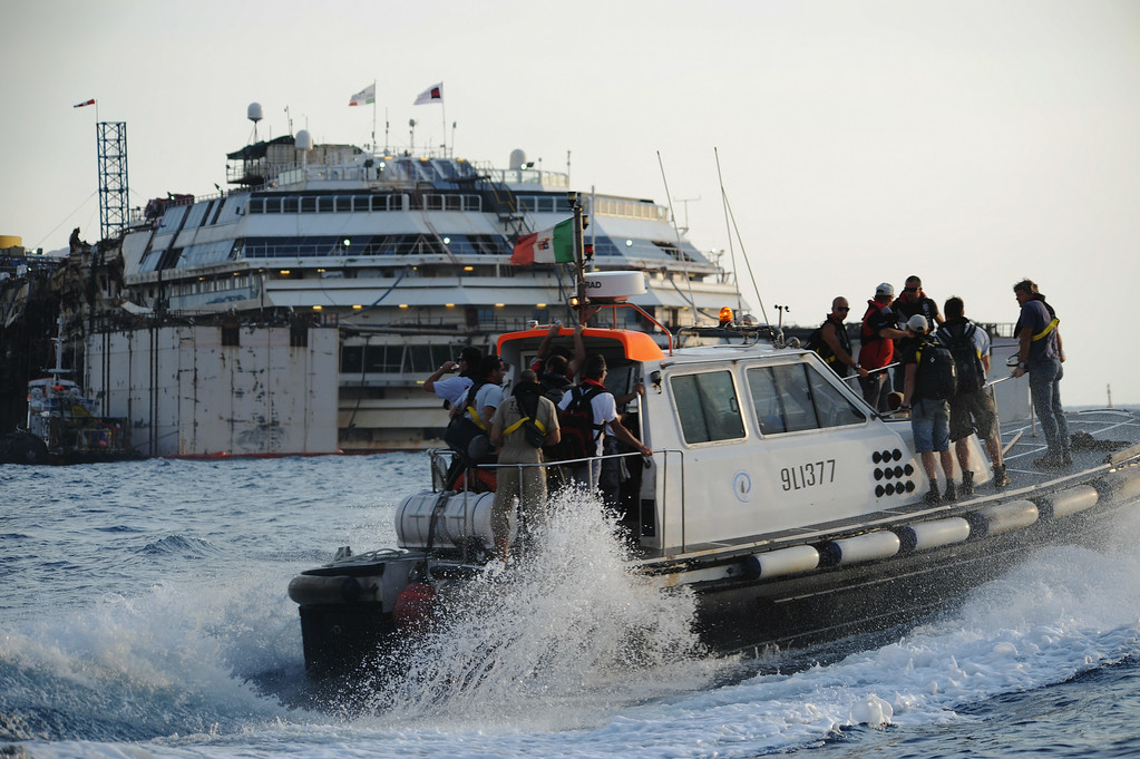 . Titan-Micoperi workers make their way out to the wrecked ship Costa Concordia before the start of the refloating operations on July 14, 2014 in Isola del Giglio, Italy. On the first day of the operation the wreck will be partially refloated by 2 metres from the platfoms that support it and will then be moved approximately 30 metres to the east. The wreck will be held in position by tugs and moored by anchors with steel cables. The refloating operation is expected to take up to a week before the wreck is towed to the port of Genoa for dismantling. (Photo by Laura Lezza/Getty Images)