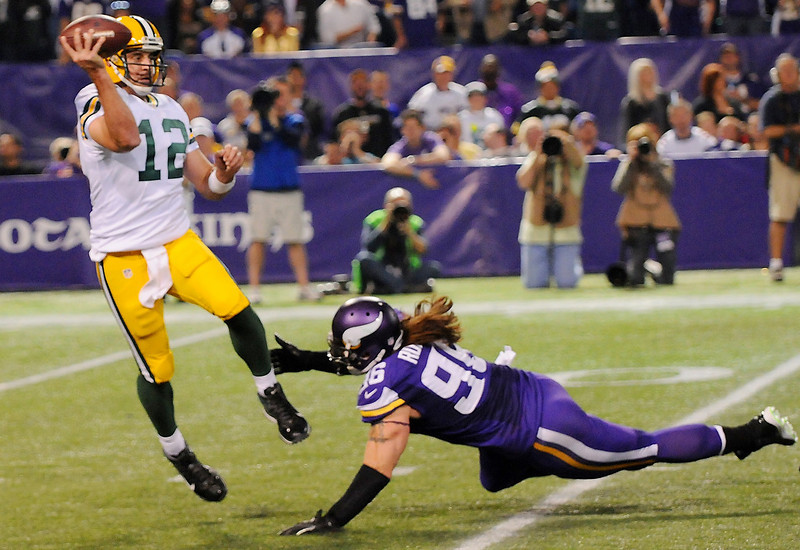 . Green Bay quarterback Aaron Rodgers avoids Minnesota defensive end Brian Robison  to complete a pass in the third quarter. (Pioneer Press: John Autey)