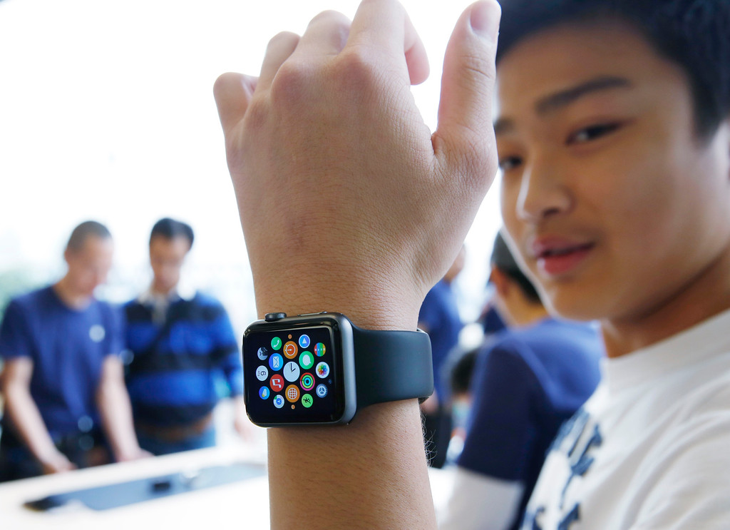 . A customer tries on an Apple Watch at an Apple Store in Hong Kong Friday, April 10, 2015. From Beijing to Paris to San Francisco, the Apple Watch made its debut Friday. Customers were invited to try them on in stores and order them online. (AP Photo/Kin Cheung)