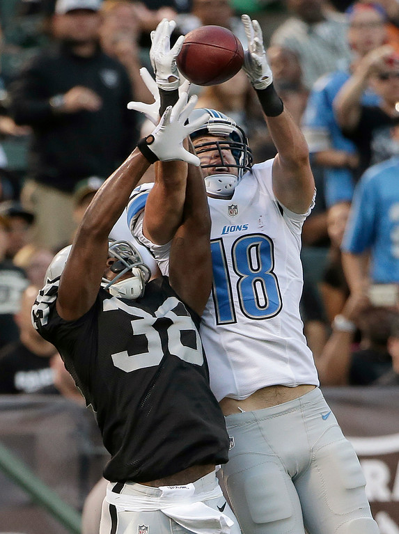 . Detroit Lions wide receiver Kris Durham (18) catches a 4-yard touchdown pass over Oakland Raiders cornerback T.J. Carrie (38) during the first quarter of an NFL preseason football game in Oakland, Calif., Friday, Aug. 15, 2014. (AP Photo/Marcio Jose Sanchez)
