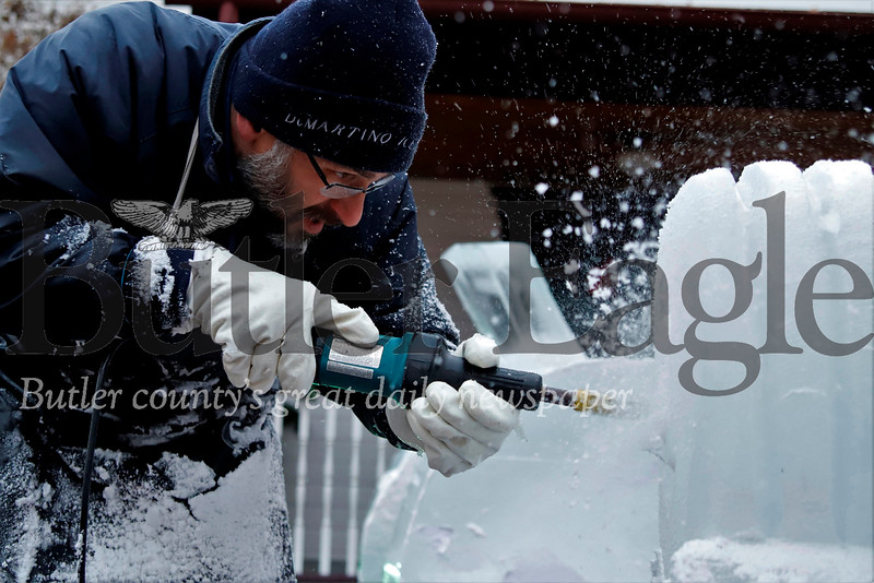 Robert Higareda of DiMartino Ice Company puts the finishing touches on an ice sculpture of a tractor. Seb Foltz/Butler Eagle